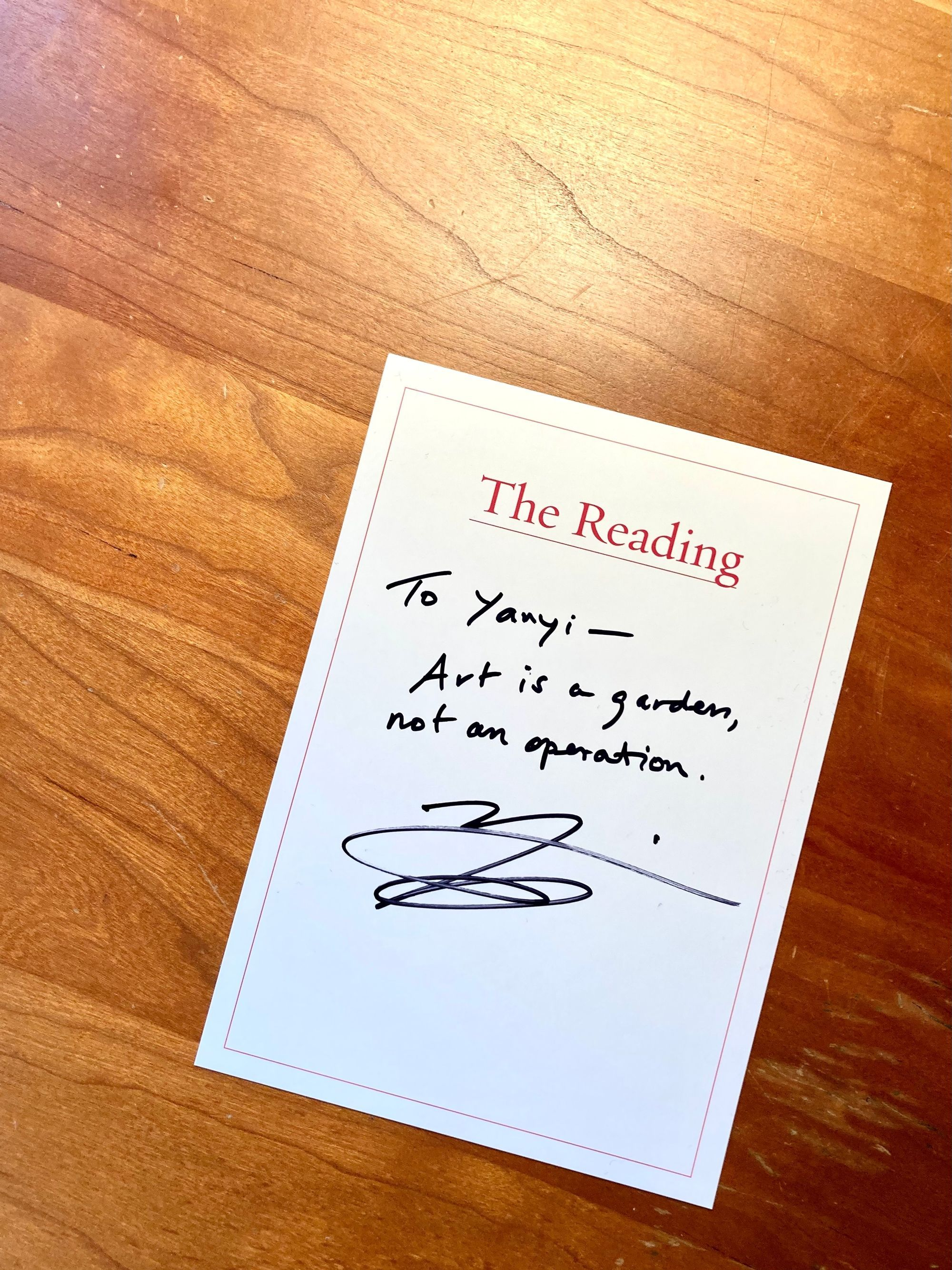 """Image: A handwritten card from The Reading, signed by Yanyi, with the note: """"To Yanyi— Art is a garden, not an operation,"""" sits on a blond wood desk."""