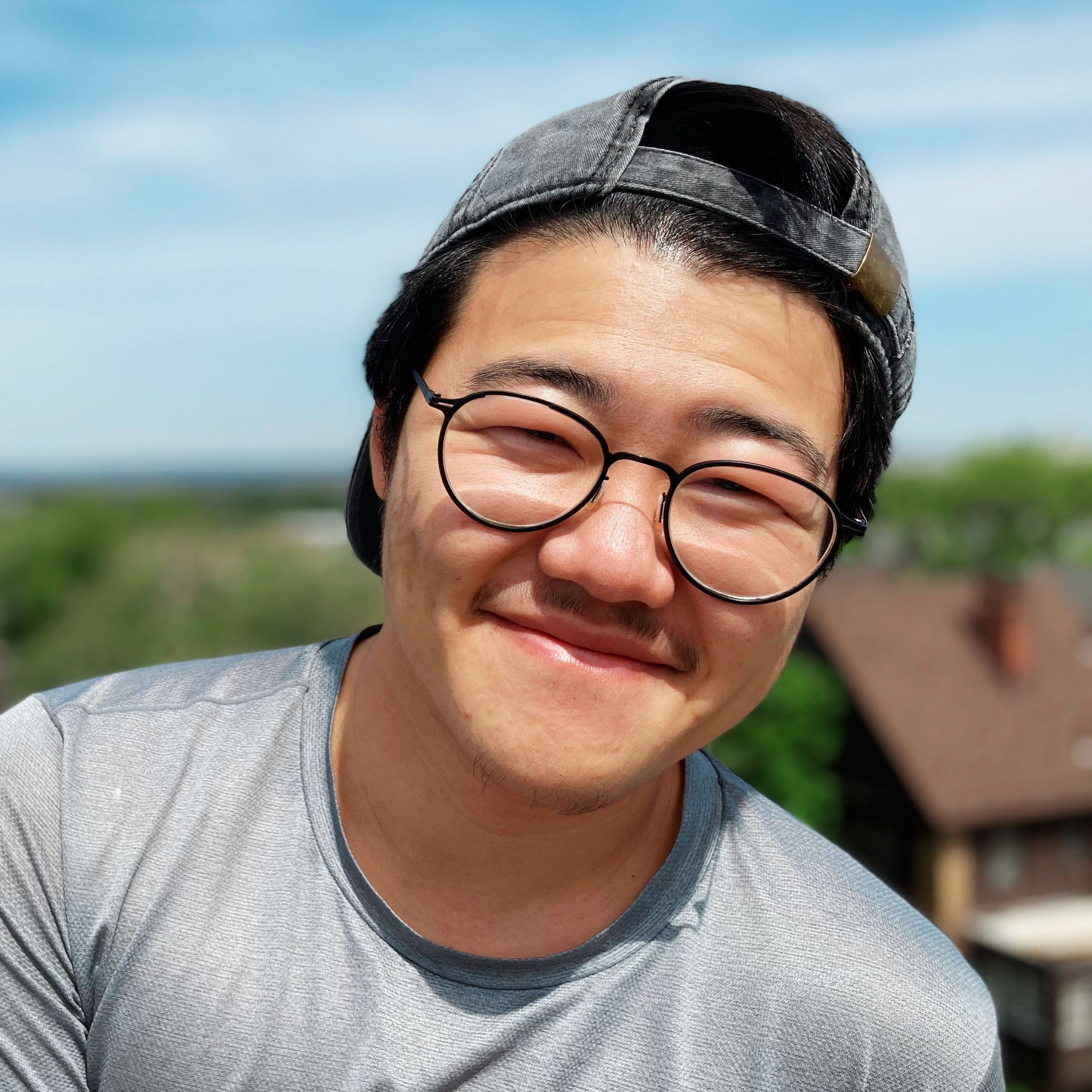 Photo: A headshot of me, Yanyi, from the chest up in front of high-rise view looking over a residential part of a city. I'm wearing a grey baseball cap backwards and a grey athletic shirt. I have short black hair and am smiling into the camera on this sunny day!